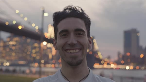 Hand-held shot of a young man laughing looking at camera outside in New York Royalty-free stock video