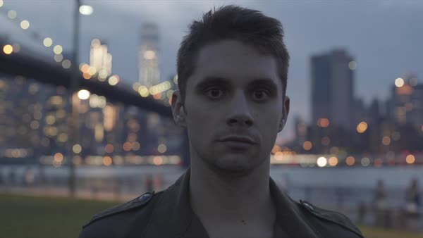 Hand-held shot of a young man looking at camera at dusk in New York Royalty-free stock video