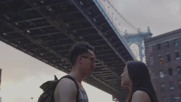 Hand-held shot of a young couple talking under Manhattan Bridge Royalty-free stock video