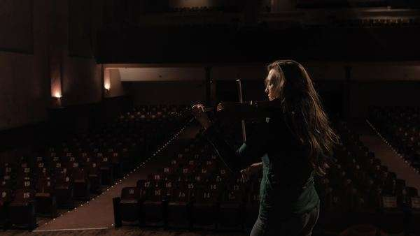 Girl plays violin in the spotlights of an beautiful old theatre.  Great for anything related to do with music, performance, or youth in general. Royalty-free stock video