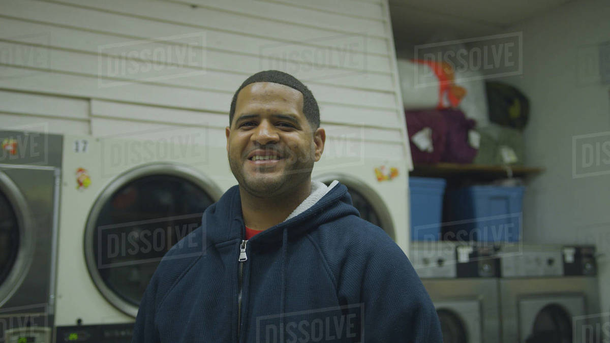Portrait of a smiling man standing in laundromat Royalty-free stock photo