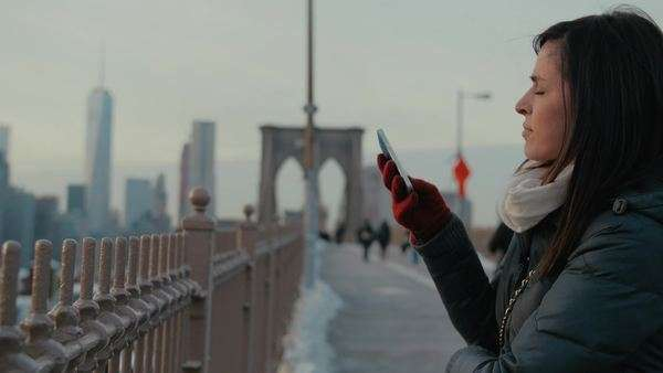 Attractive young woman takes a photo on her smartphone while standing on the Brooklyn Bridge with Manhattan in the background Royalty-free stock video