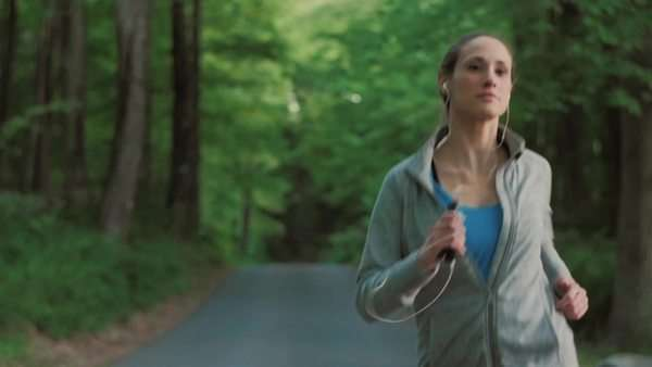 Medium shot of a young woman jogging in a forest Royalty-free stock video