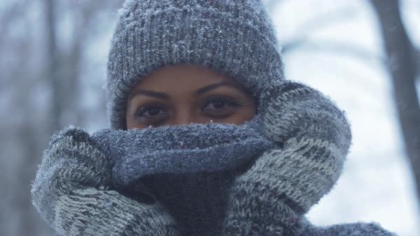 Beautiful girl smiling behind sweater at camera in snowstorm Royalty-free stock video