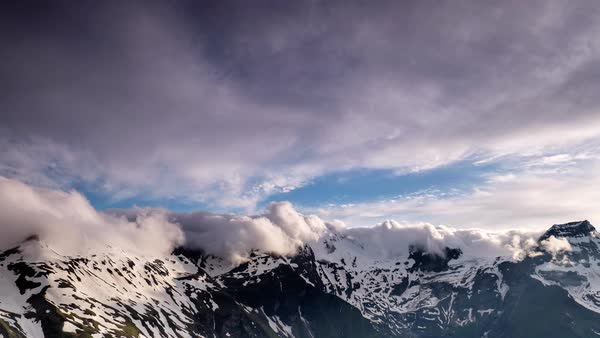 Timelapse of clouds rolling over snowy mountain peaks Royalty-free stock video