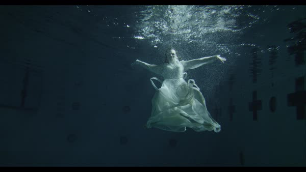 Slow motion shot of woman in white dress floating underwater Royalty-free stock video