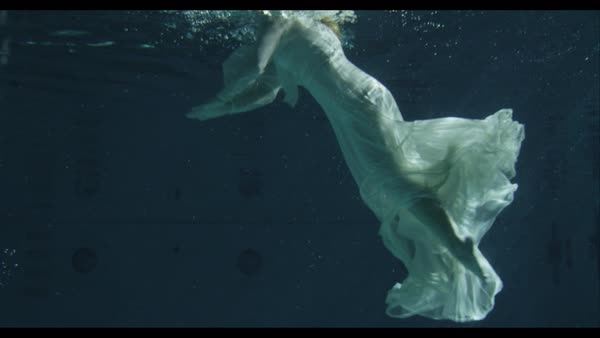 Slow motion shot of woman in white gown floating underwater Royalty-free stock video