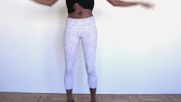 Hand-held shot of a young woman doing jumping jacks against white wall Royalty-free stock video