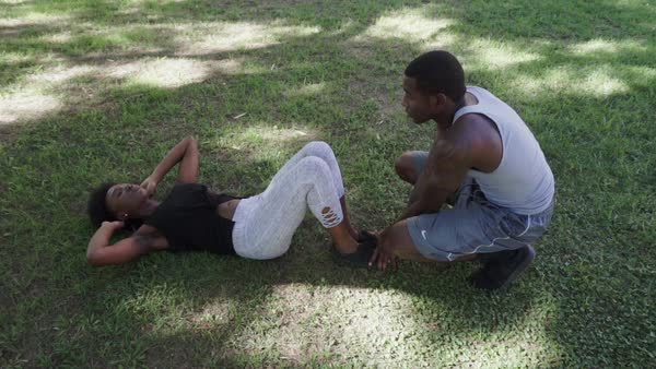Hand-held shot of a young man helping young woman doing sit-ups in park Royalty-free stock video