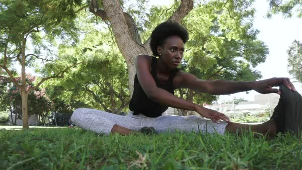 Hand-held shot of a young woman stretching in park Royalty-free stock video