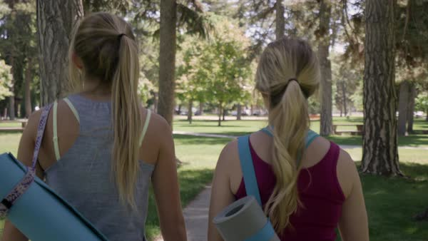Friends Walk And Talk Together On Park Path Through Tall Trees, On Way To Yoga Class Royalty-free stock video