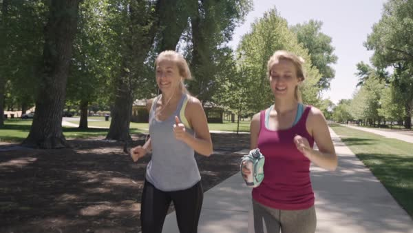 Young Women Jog In The Park Together, One Listens To Music On Smartphone, They Both Look Around With Smiles, Enjoying The Scenery (Slow Motion Steadicam Shot) Royalty-free stock video