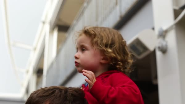 Dad holds his little boy on his shoulders on game day at a professional stadium (slow motion close-up) Royalty-free stock video