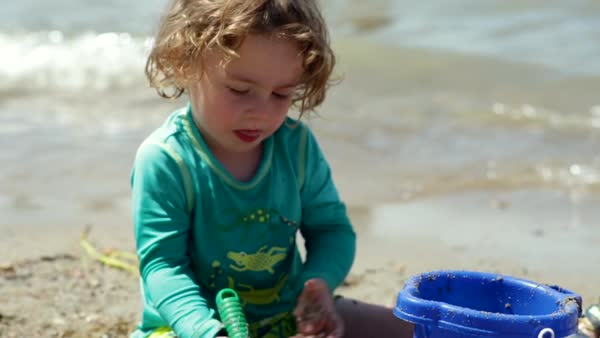 Little boy plays with sand toys at beach, gentle waves crash behind him, slow motion Royalty-free stock video