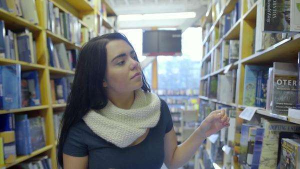 Teen checks her smart phone to find the right book Royalty-free stock video