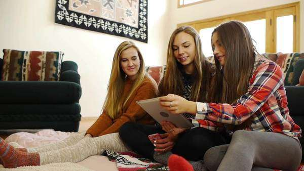 Animated Teenage Girls Using Digital Tablet; Friend Arrives With Cookies Royalty-free stock video