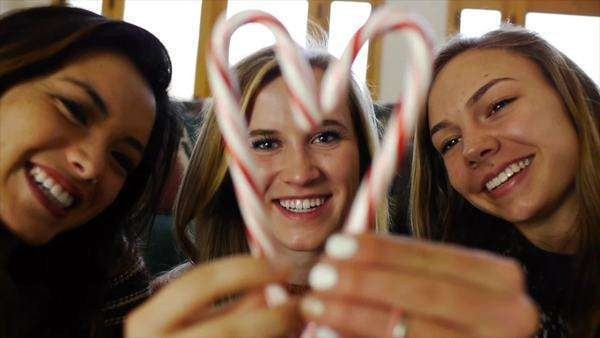 Teen Girl Framed By Friends In A Candy Cane Heart Blows A Kiss Royalty-free stock video