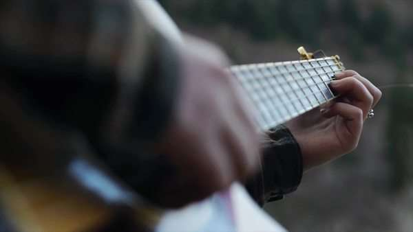Close Up Of Cute Teen Outdoors In A Hoody Softly Strumming Her Guitar Royalty-free stock video