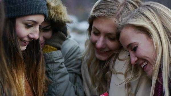 Group Of Bundled-Up Teen Girls Laughing At A Smart Phone Royalty-free stock video