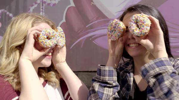 Two teens cover their eyes with donuts and make silly faces at the camera and at each other Royalty-free stock video