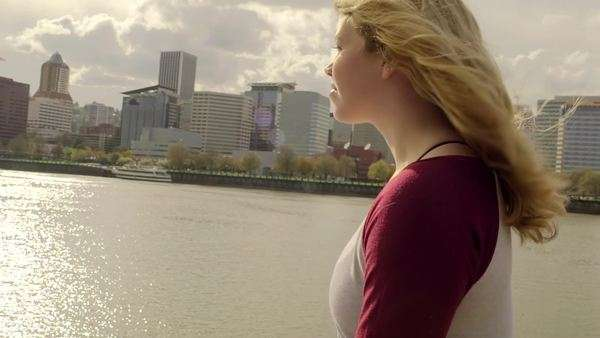 Slow motionprofile shot of carefree young woman walking along river, across from city Royalty-free stock video