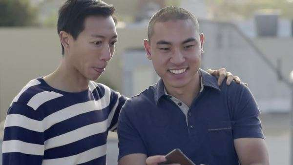 Gay couple take a selfie together on a rooftop in San Francisco, then enjoy looking at it Royalty-free stock video