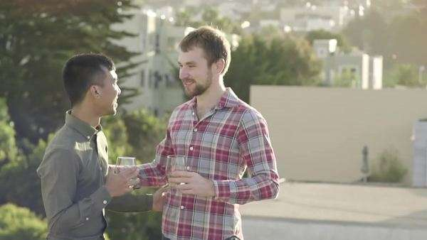 Gay couple enjoy drinks together on a rooftop, they hug and flirt, their friend asks to take their photo Royalty-free stock video