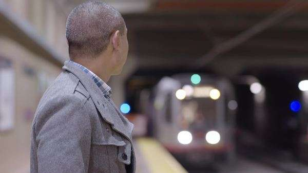 Man smiles at camera, then turns to look at approaching train Royalty-free stock video