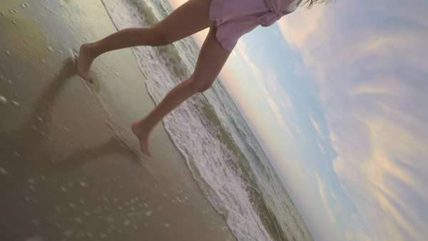 Unique perspective of young woman's legs as she runs along beach, using gopro stick Royalty-free stock video