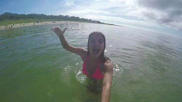Teenage girl uses GoPro stick in ocean, she dives underwater with GoPro and poses with a thumbs up and peace sign Royalty-free stock video