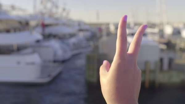 Young woman holds up peace sign, from moving boat, as a greeting or goodbye to marina full of yachts and sailboats Royalty-free stock video