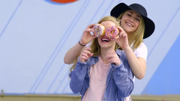 Teen covers her friend's eyes with donuts, girl holds up peace signs, thumbs up Royalty-free stock video