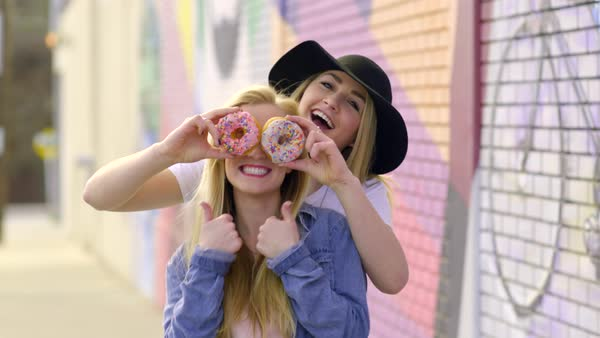 Fun teens pose with donuts, they cover their eyes and make funny faces, and hold up peace signs and give thumbs up Royalty-free stock video