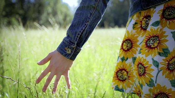 Young woman walks through tall grass in slow motion (close up of her hand feeling grass) Royalty-free stock video
