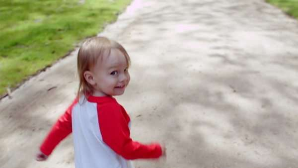 Little boy looks over his shoulder and smiles at camera, then runs down sunny park path Royalty-free stock video