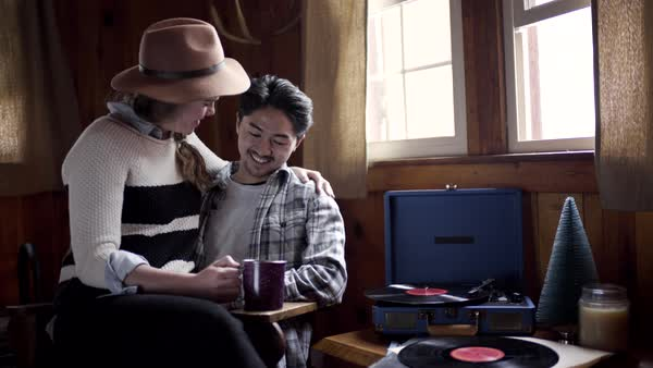 Affectionate couple enjoy listening to christmas music on record player, they talk/flirt Royalty-free stock video