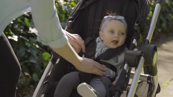 Mother buckles her baby girl into her stroller, then begins to push stroller Royalty-free stock video