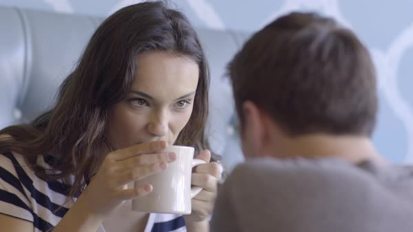 Young Woman (20s) Blows On Her Hot Coffee, Takes A Sip, Flirts With Her Boyfriend Across The Table, In Coffee Shop Royalty-free stock video