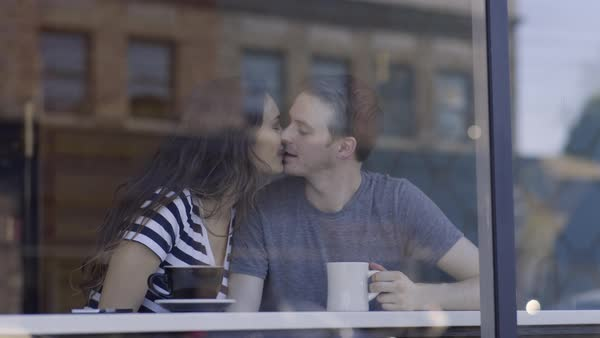 Cute Couple Sit At Bar In Coffee Shop Window, Man Enjoys View, Woman Gets His Attention And Gives Him A Kiss, They Flirt And Laugh  Royalty-free stock video