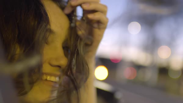 Closeup Portrait Of Carefree Woman Leaning Out Car Window At Night In City, She Smiles And Brushes Her Hair Behind Her Ear Royalty-free stock video
