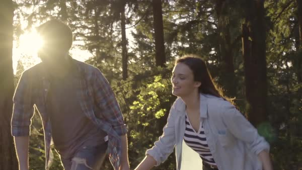 Slow Motion Follow Shot Of Cute Couple Holding Hands And Running Through Trees At Sunset, Backlit Royalty-free stock video