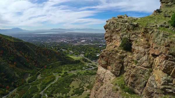 Epic aerial fly by of mountain cliffs above Provo Utah with fall colors of trees in view Royalty-free stock video