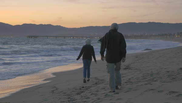 Happy mature 60s couple running and playing along upscale beachfront at sunset. Retired fit elderly caucasian man and woman enjoying vacation exploring coast at dusk Royalty-free stock video