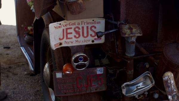 Man with desert camouflage pants stands next to an antique rusted truck with You've Got A Friend in Jesus license plate with additional old rusted antique items. Antique gas can, jack, and other rusted metal objects hang from the back dolly shot. Royalty-free stock video
