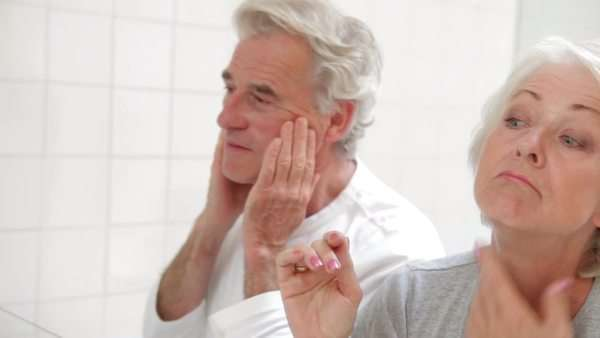 Senior couple checks condition of skin in bathroom mirror. Royalty-free stock video