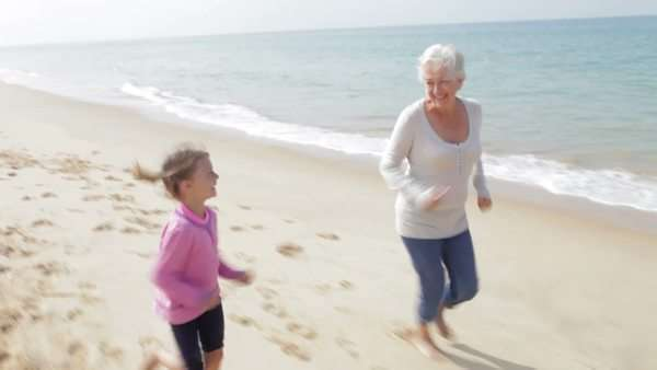 Grandmother and granddaughter run along the beach together. Royalty-free stock video