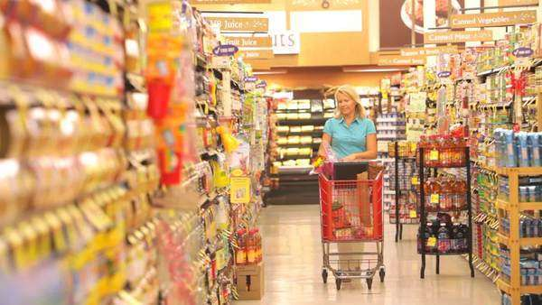 Woman walks down supermarket aisle before taking bottle from shelf, reading ingredients and putting into shopping trolley. Royalty-free stock video