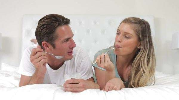 Couple lying on bed eating a spoonfuls of yoghurt and looking happy. Royalty-free stock video