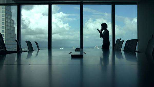 Silhouette of businesswoman alone in boardroom talking on mobile phone. Royalty-free stock video