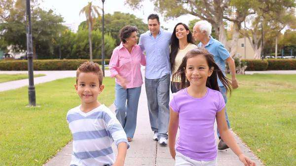 Multi-generation family walking through park together - the children walking on ahead. Royalty-free stock video